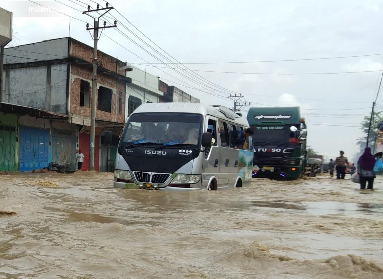 Foto menunjukkan Mobil Isuzu menerjang banjir