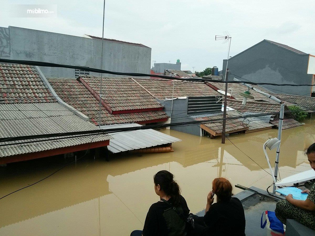Foto menunjukkan banjir merendam rumah warga hingga atap