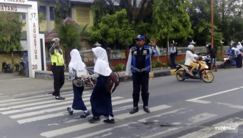Gambar ini menunjukkan anak-anak sedang menyebrang dan terlihat ada pak petugas polisi