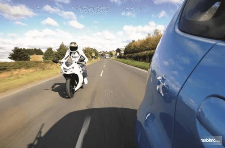 Gambar ini menunjukkan seorang pengendara sepeda motor ingin menyalip mobil