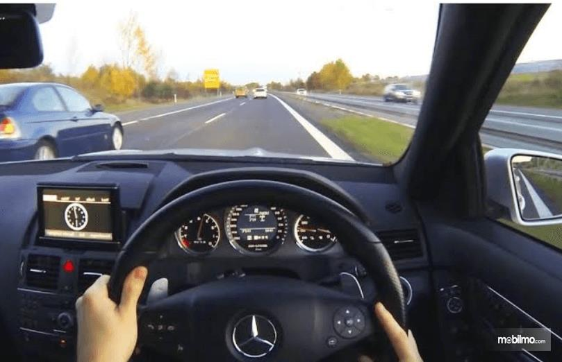 Gambar in menunjukkan seorang pengemudi sedang menyalip mobil lain