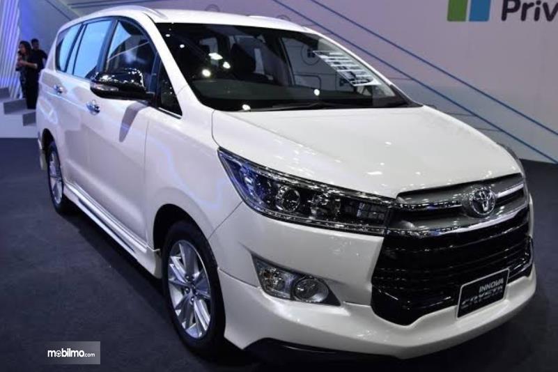 Gambar ini menunjukkan mobil Toyota Innova Crysta warna putih tampak samping