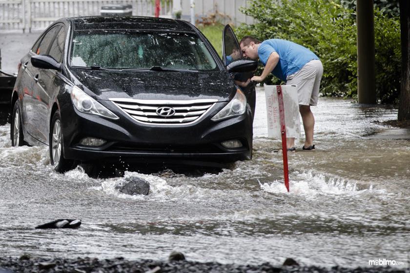 Foto menunjukkan mobil Hyundai parkir di atas genangan