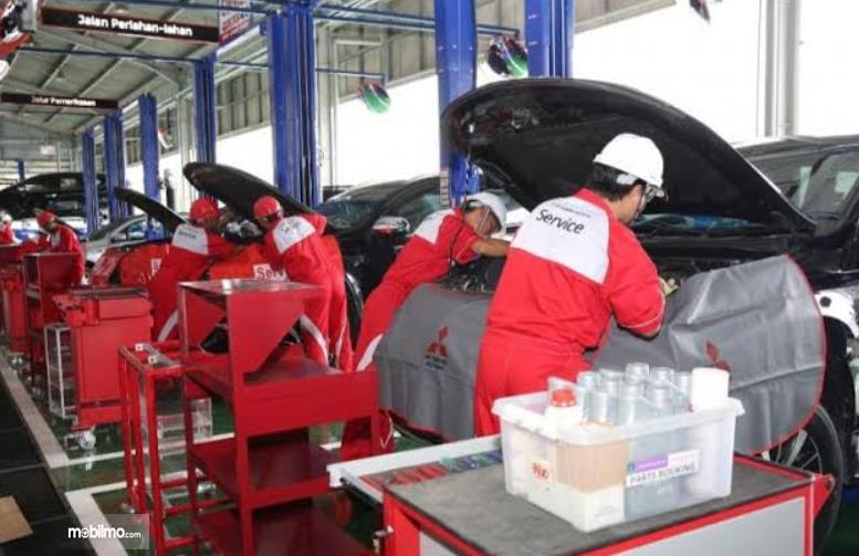 Gambar ini menunjukkan mekanik Mitsubishi sedang memeriksa mobil