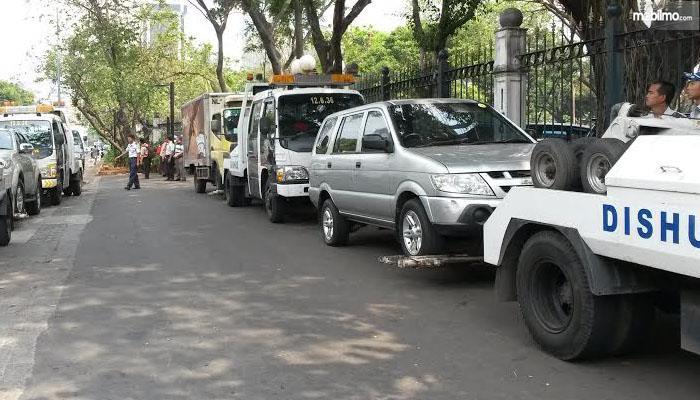 Foto menunjukkan mobil diderek petugas