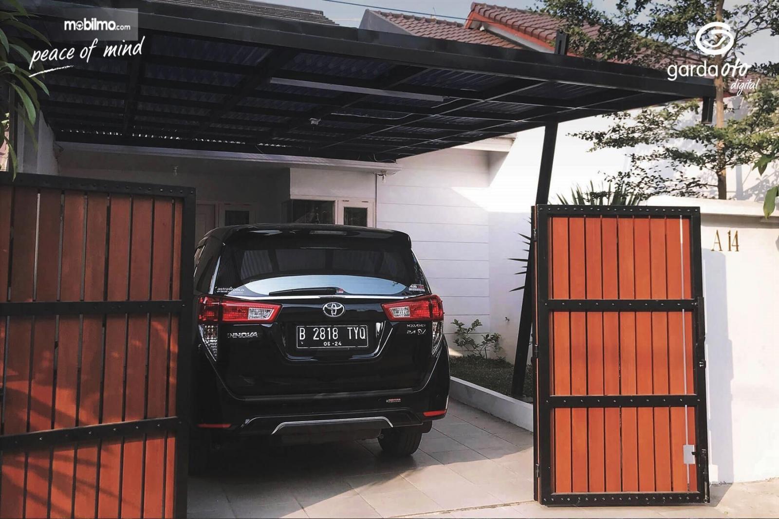 Foto menunjukkan mobil Toyota Innova diparkir di garasi rumah