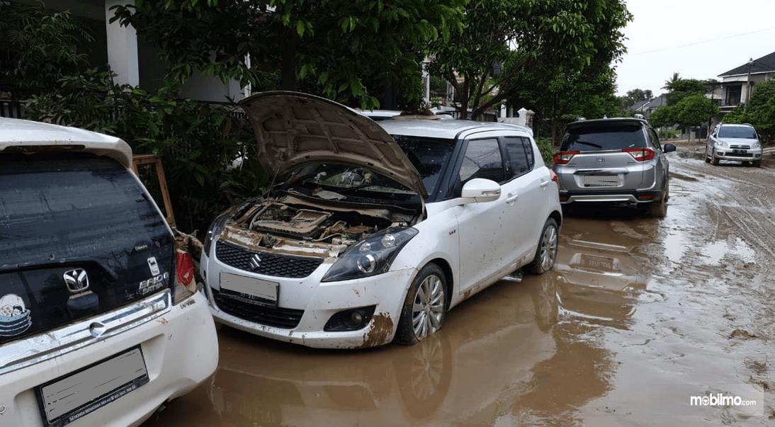 Gambar ini menunjukkan beberapa mobil habis terendam banjir