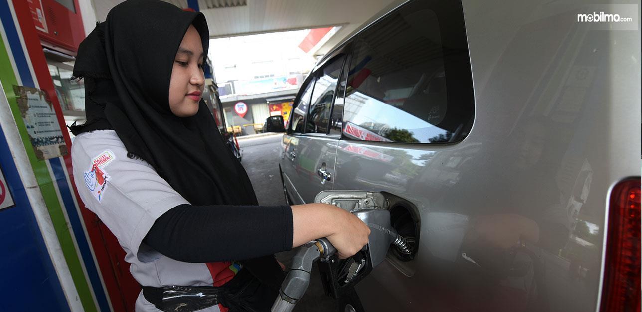 Foto menunjukkan pegawai SPBU sedang mengisi BBM Biosolar B30 ke mobil konsumen