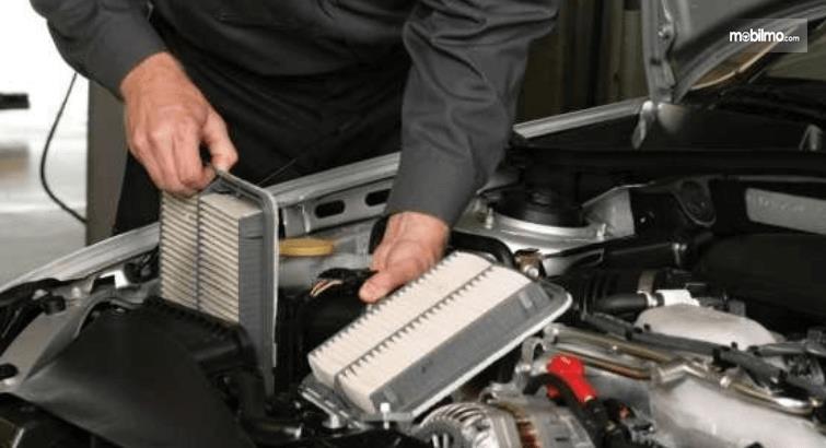 Gambar ini menunjukkan seseorang mengganti filter mesin mobil