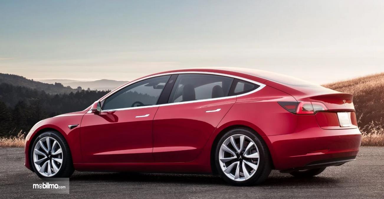 Gambar ini menunjukkan mobil Tesla model 3 warna merah tampak samping