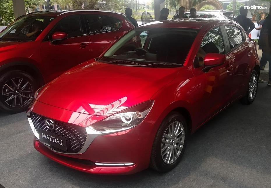 Gambar ini menunjukkan mobil Mazda2 warna merah