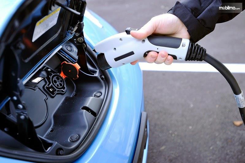 Foto menunjukkan proses pengisian daya listrik untuk mobil listrik Nissan LEAF