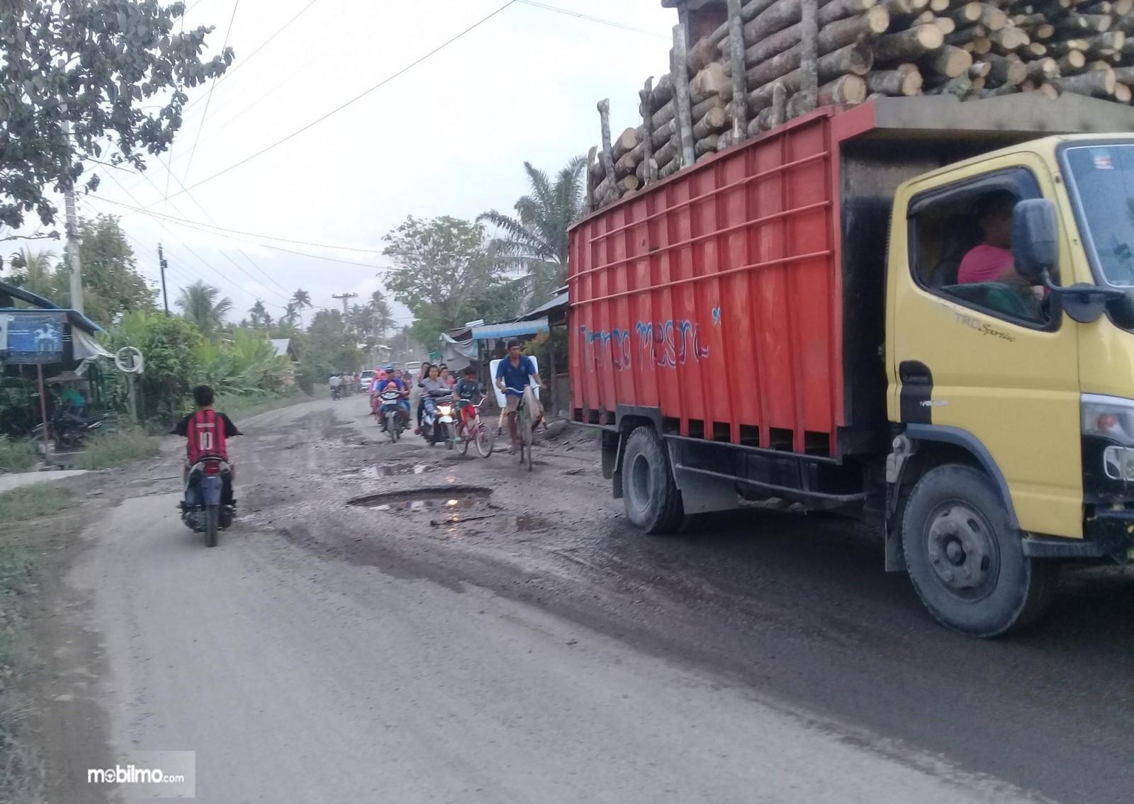 Foto menunjukkan truk ODOL melintas di jalan rusak
