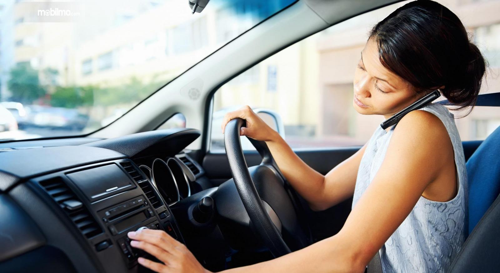 Foto menunjukkan pengemudi wanita menggunakan HP saat mengemudi