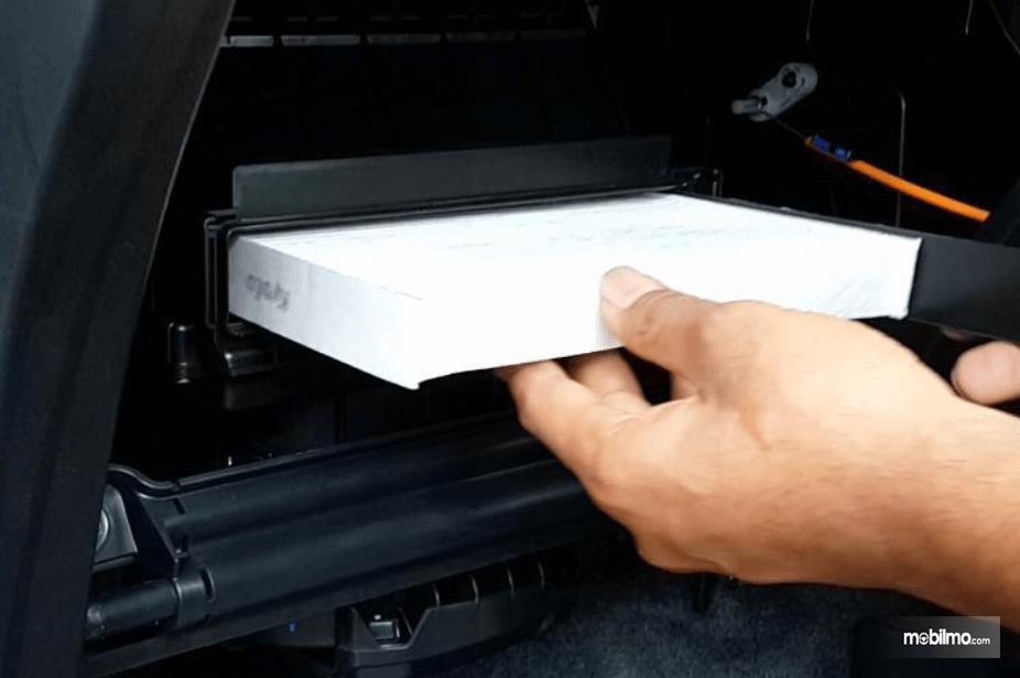 Gambar ini menunjukkan seorang tangan memegang filter AC Mobil