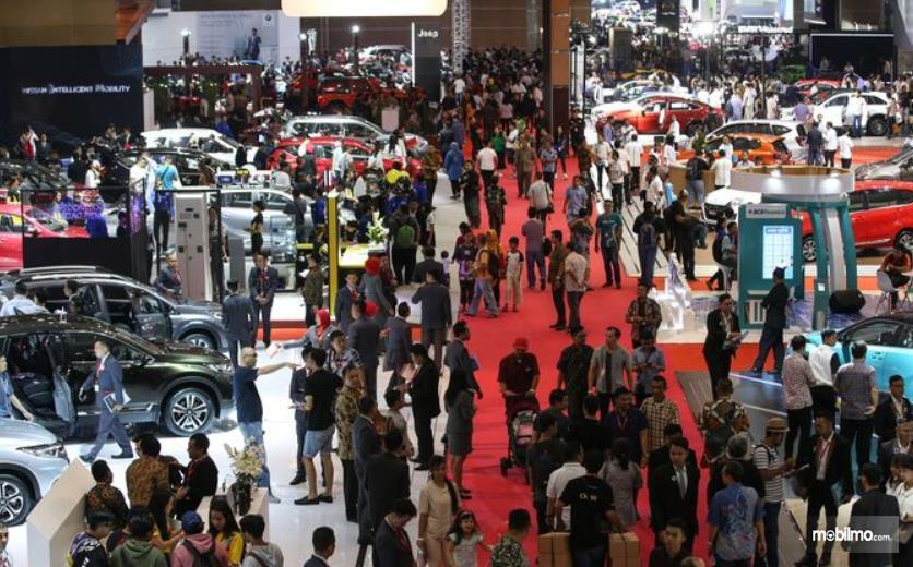 Gambar ini  menunjukkan acara IIMS dengan banyak orang dan mobil