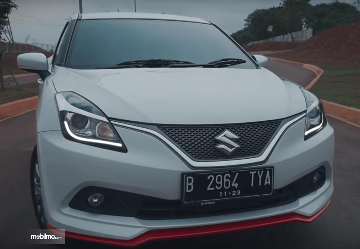 Gambar ini menunjukkan bagian depan mobil Suzuki Baleno Hatchback AT 2018