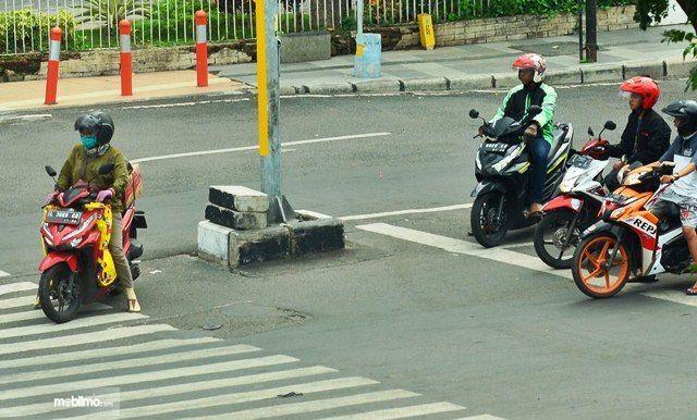 Gambar menunjukkan pengemudi motor melanggar marka Zebra Cross