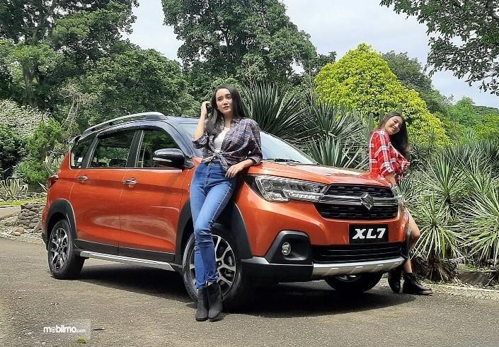 Foto Suzuki XL7 tampak dari samping depan bersama dua orang model
