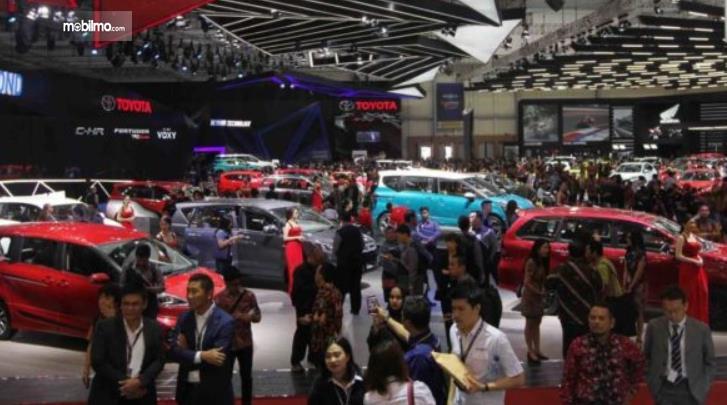 gambar ini menunjukkan banyak orang berada di pameran mobil