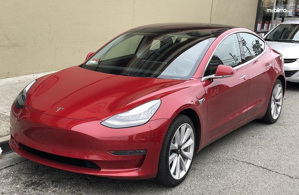 Foto Tesla Model 3 warna merah tampak dari samping depan