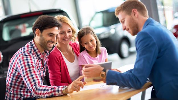 Foto menunjukkan seorang sales memberikan penjelasan soal mobil kepada kustomer