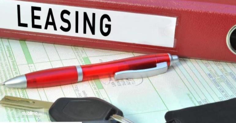 Gambar ini menunjukkan kunci mobil, bulpen dan tulisan leasing