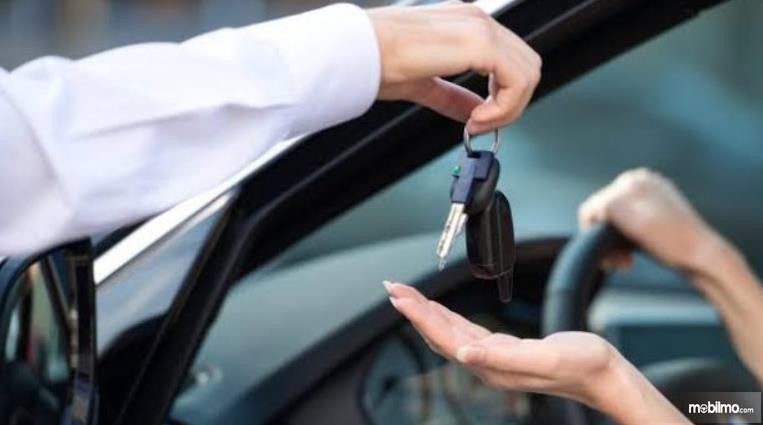 Gambar ini menunjukkan sebuah tangan menyerahkan kunci pada seseorang di dalam Mobil