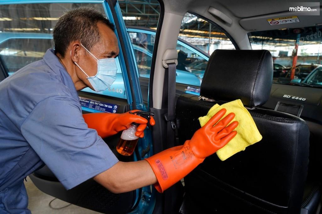 Foto menunjukkan seorang Pengemudi taksi Blue Bird membersihkan kabin mobil