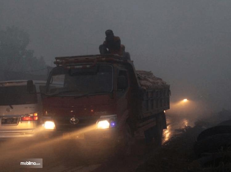 Gambar ini menunjukkan mobil truk dan kendaraan lain menyalakan lampu depan