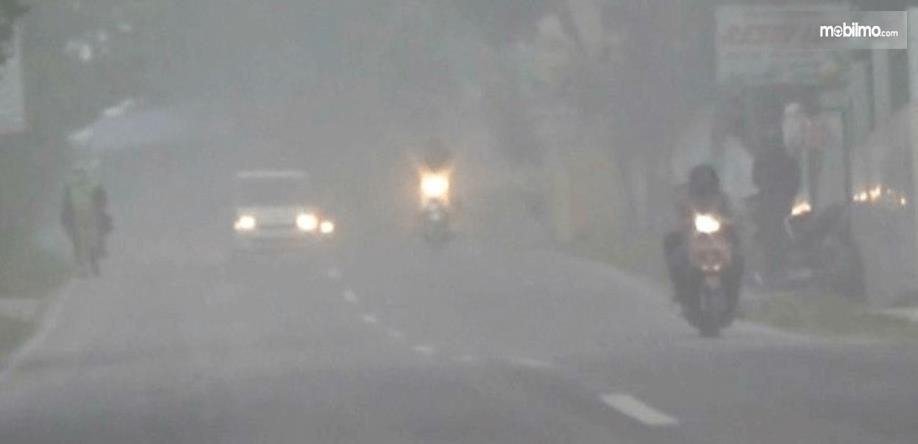 gambar ini menunjukkan 2 motor dan 1 mobil sedang melaju dalam hujan abu vulkanik