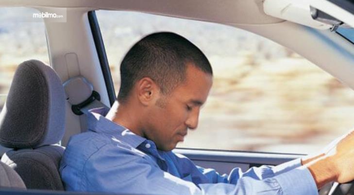 Gambar ini menunjukkan seorang pengemudi sedang tertidur