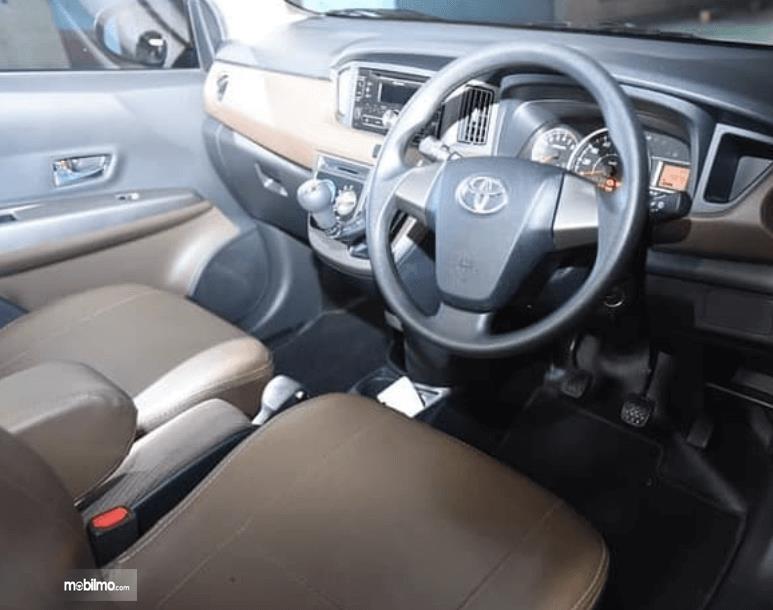 Gambar ini menunjukkan bagian bangku depan, kemudi dan dashboard mobil Toyota Calya 1.2 G MT 2017