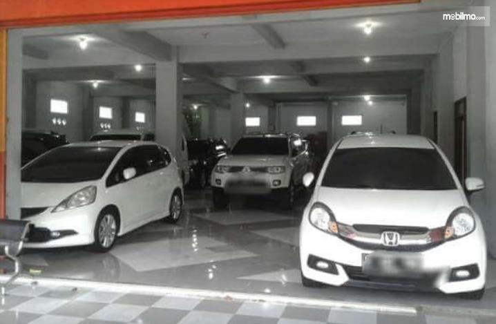 gambar ini menunjukkan beberapa mobil dalam Showroom mobil bekas