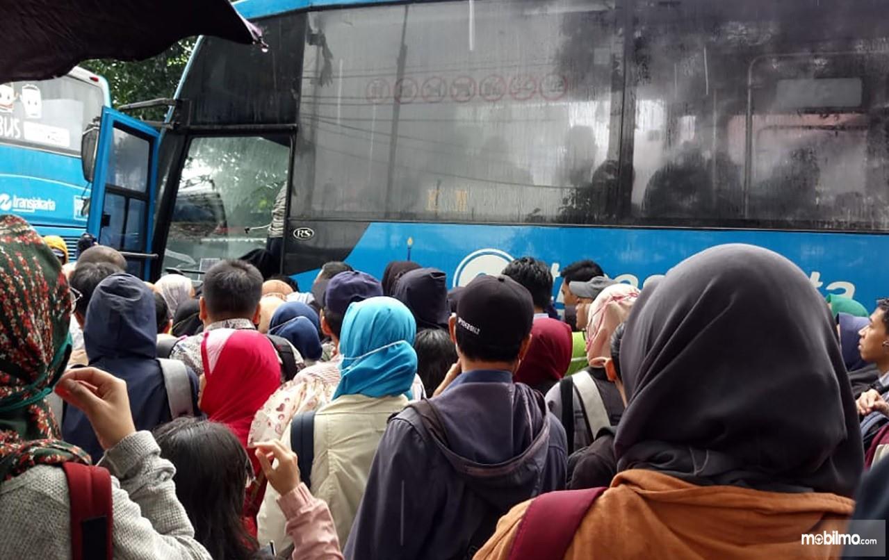 Foto menunjukkan penumpang bersiap naik bus