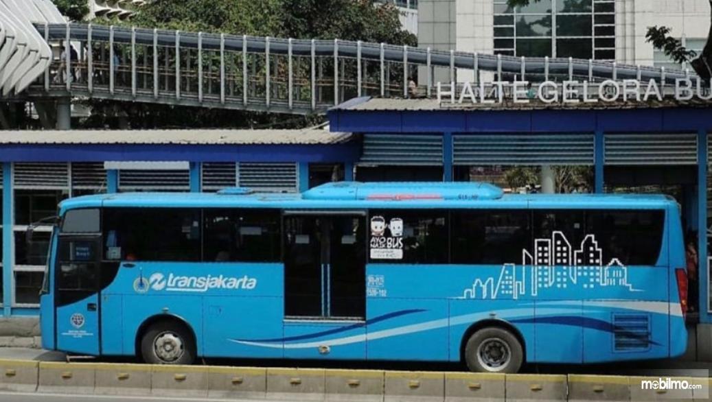 Gambar ini menunjukkan bus Transjakarta warna biru di halte bus