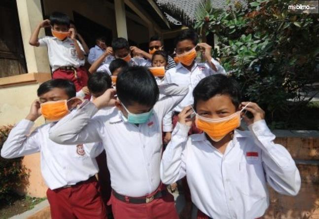 Gambar ini  menunjukkan banyak anak sekolah sedang menggunakan masker