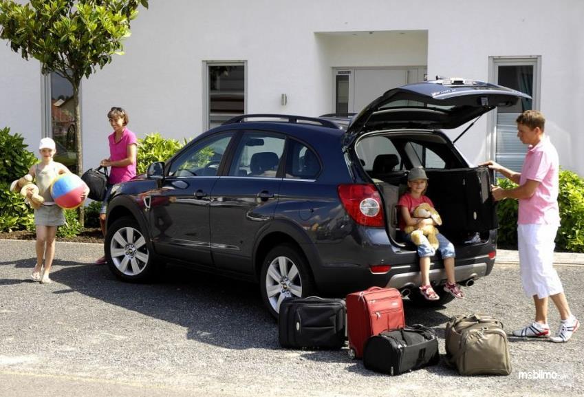 Gambar ini menunjukkan sekeluarga sedang siap naik mobil untuk liburan