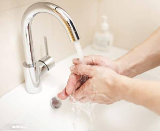 gambar ini menunjukkan 2 tangan sedang dicuci di bawah air mengalir