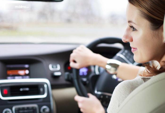 Gambar ini menunjukkan seorang wanita sedang memegang kemudi mobil