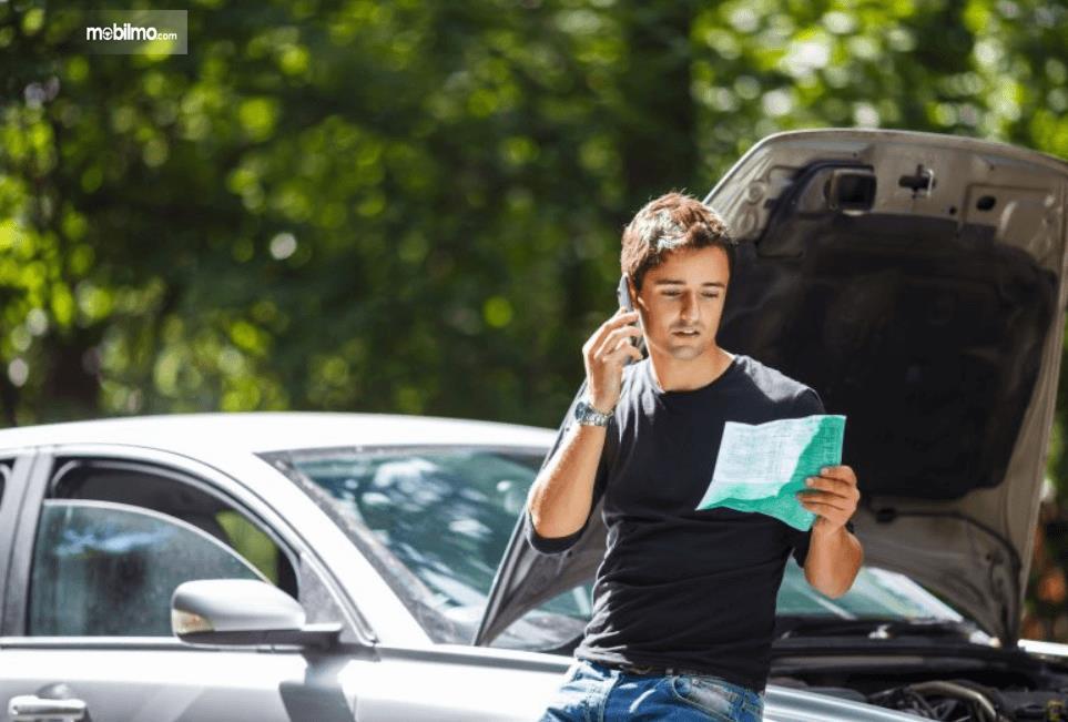 Gambar ini menunjukkan seorang pria menelpon dan melihat kertan duduk di mobil dengan kap terbuka