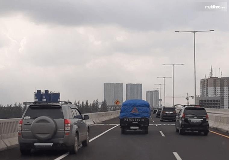 Gambar ini menunjukkan beberapa mobil melaju di jalanan dan satu mobil di bahu jalan