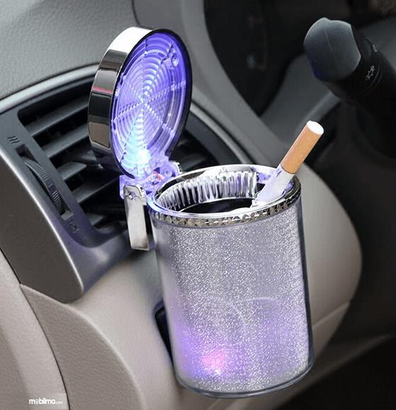 Gambar ini menunjukkan rokok ditempatkan pada asbak di mobil