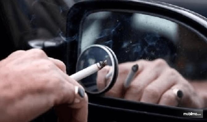 Gambar ini menunjukkan sebuah tangan memegang rokok dekat spion mobil