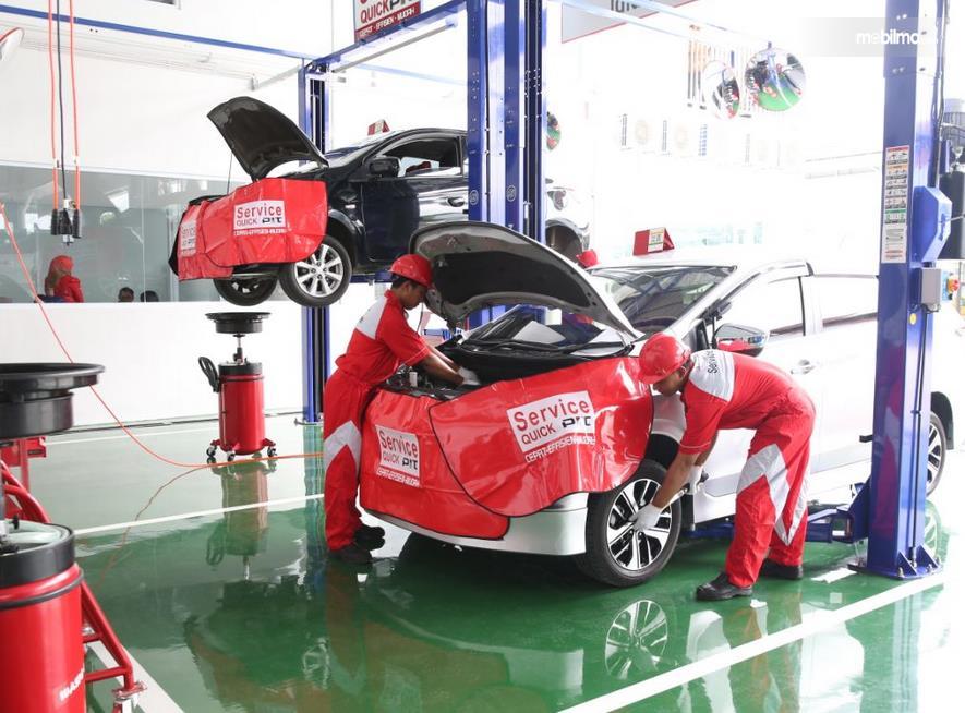 Gambar ini menunjukkan beberapa mekanik sedang memeriksa mobil Mitsubishi