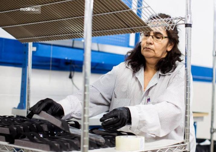 Gambar ini menunjukkan seorang wanita sedang produksi alat kesehatan