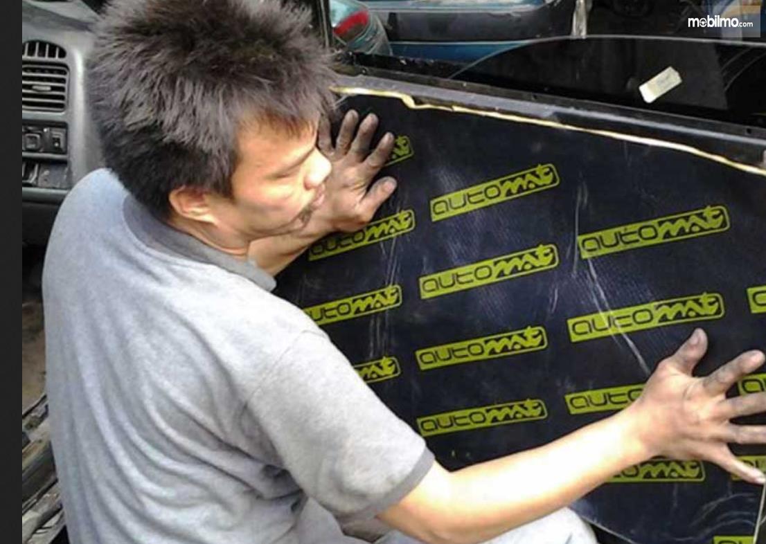 Gambar ini menunjukkan seorang pria sedang memasang peredam pada pintu mobil