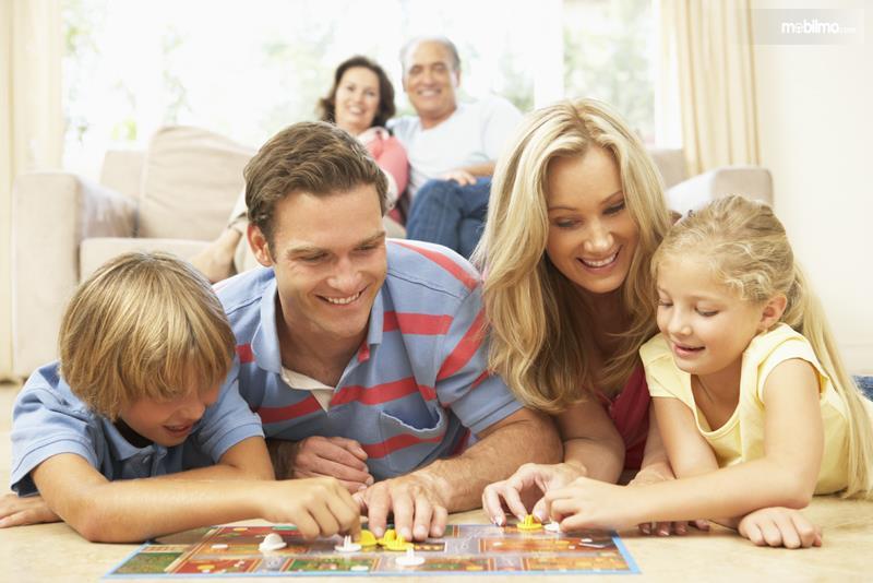 Foto menunjukkan suasana bermain monopoli bersama keluarga