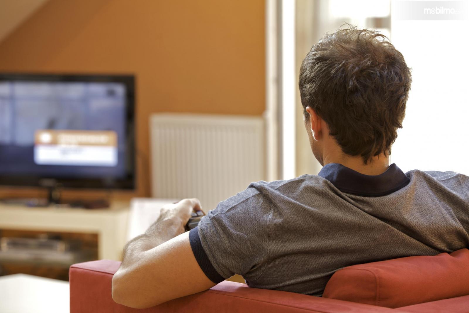 Foto menunjukkan menonton film di rumah