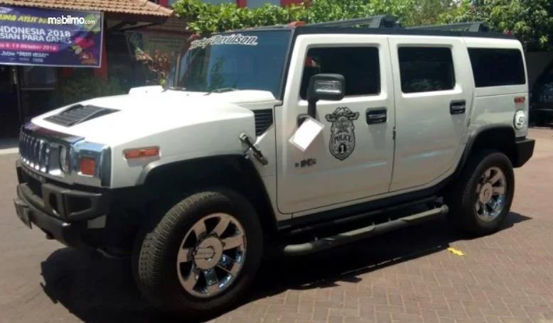 Gambar ini menunjukkan mobil Hummer H2 warna putih tampak samping
